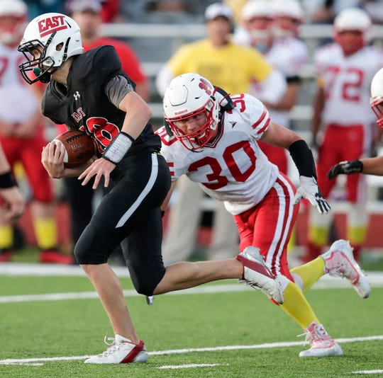 Green Bay East's quarterback Riley Jensen (18) is chased down by Seymour's Aaron Geurts (30) on Friday.