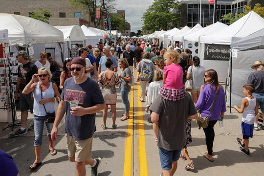 People walk the booths on Cherry Street during Artstreet Saturday, August 24, 2019, in Green Bay, Wis.