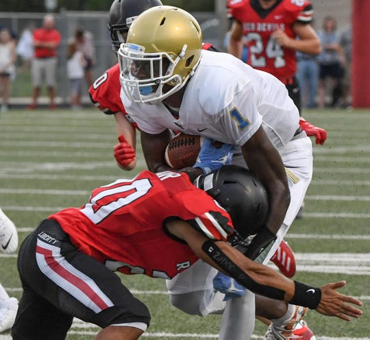 Liberty senior Carter Hair(20) tackles DW Daniel senior Brenton Benson(1) during the first quarter at Liberty High School in Liberty Friday, August 23, 2019.