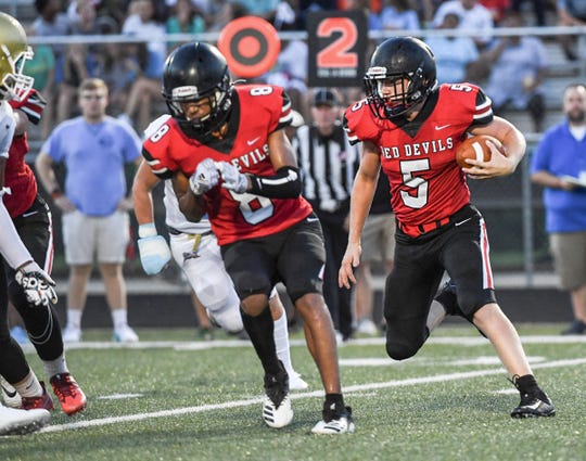 Liberty senior Luke Terry(5) runs near Liberty junior EJ Stafford(8) during the first quarter at Liberty High School in Liberty Friday, August 23, 2019.
