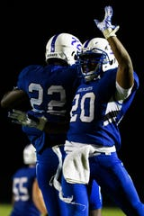 Woodmont's Joshua Kamoto (22) and Rashun Kennedy (20) celebrate during their game against Greenville Friday, Aug. 23, 2019.