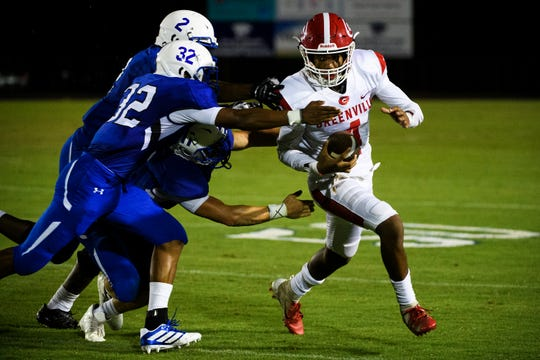 Greenville's Andre Goodman (4) tries to evade the Woodmont defense Friday night at Woodmont.