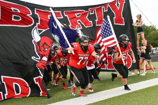 Liberty seniors Dawson Smith(77) and Brad Moore(61), right, run on the field before the game at Liberty High School in Liberty Friday, August 23, 2019.
