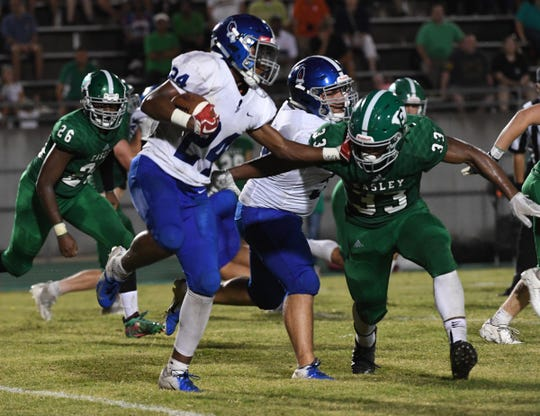 Pickens sophomore Jamorea Keith( 24) carries the ball ad Easley senior Josh Hill (33) closes in during the third quarter Friday night at Easley High School.