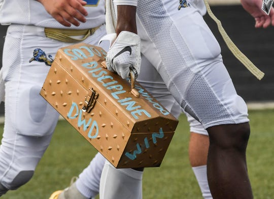 """DW Daniel players walk with a toolbox with words """"discipline, focus, and win"""" before the game at Liberty High School in Liberty Friday, August 23, 2019."""