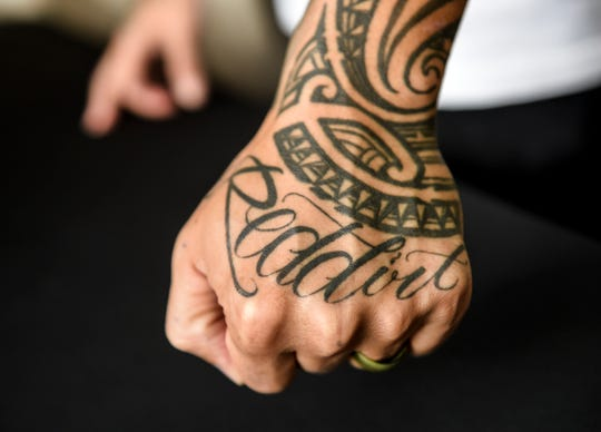 Danny Baisa displays a tattoo of his business name at the Reddirt Tattoo shop in Tumon on Aug. 23, 2019.