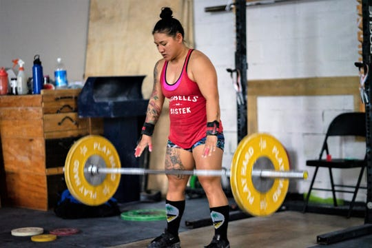 Jacinta Sumagaysay drops a weight during a workout at Chamorri Crossfit gym in Tamuning on Aug. 22, 2019.