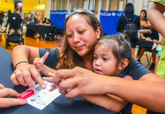 Claudine Flores, 2, gets a helping hand from her mother, Valerie Sayama Flores, while filling in a fingerprint chart during the annual KidCare ID event at the Agana Shopping Center on Saturday, Aug. 24, 2019. A photo and identifying information of children were added to free booklets, provided to parents at the event, that could be used by emergency providers if the child should be reported missing. Various vendors and government agencies handed out free product samples and information to visitors. Several lucky participants also got to compete in a barbecue rib- and spaghetti-eating contest. For colelction of images captured at the event, log onto GuamPDN.com.