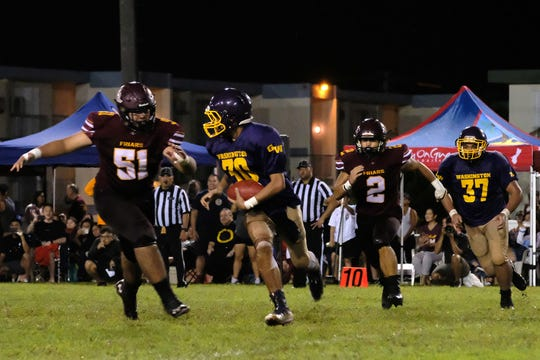 George Washington Geckos 30 Enrique Macias is chased by Father Duenas Friars 51 Elijah Calvo the during the high school football game at GW field Aug. 23, 2019.