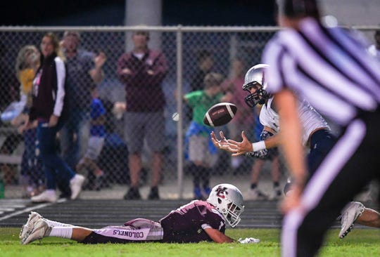 Reitz's Jaydon Summers (9) catches a touchdown pass as defender Henderson's Colton Evans (1) lies on the ground as the Reitz Panthers play the Henderson County Colonels at Henderson's Colonel Field Friday evening, August 23, 2019.