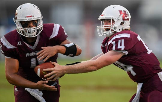 Henderson County quarterback Sam Elliott (14) hands off to teammate Layton Fletcher (4) as the Reitz Panthers play the Henderson County Colonels at Henderson County's Colonel Field Friday evening, August 23, 2019.