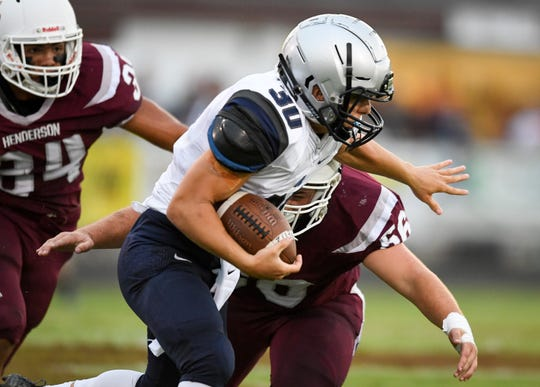 Reitz's Alex Mitchell (30) picks up some ground yards as he fends off tackler Henderson's Jackson Williams (56) as the Reitz Panthers play the Henderson County Colonels at Henderson's Colonel Field Friday evening, August 23, 2019.