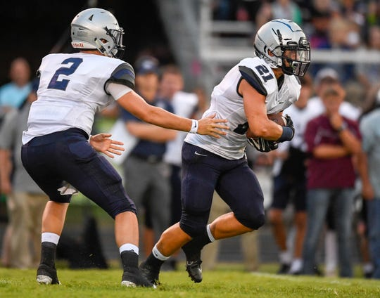 Reitz quarterback Reid Brickey (2) hands off to Chris Thacker (21) as the Reitz Panthers play the Henderson County Colonels at Henderson's Colonel Field Friday evening, August 23, 2019.