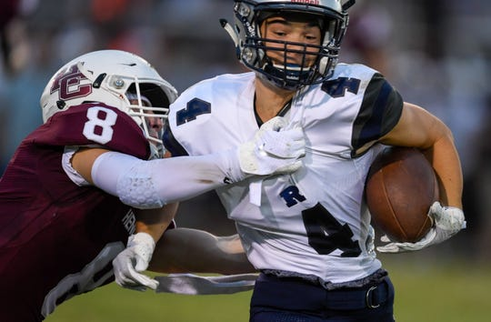 Reitz's Jackson Dassel (4) digs for yards as Henderson's Ben Dalton (8) drags him down as the Reitz Panthers play the Henderson County Colonels at Henderson's Colonel Field Friday evening, August 23, 2019.