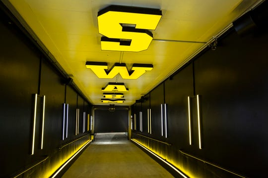 """Yellow letters that spell out """"Swarm"""" on the ceiling in the tunnel that leads towards the field is pictured during a behind the scenes tour, Friday, Aug. 23, 2019, at Kinnick Stadium in Iowa City, Iowa."""