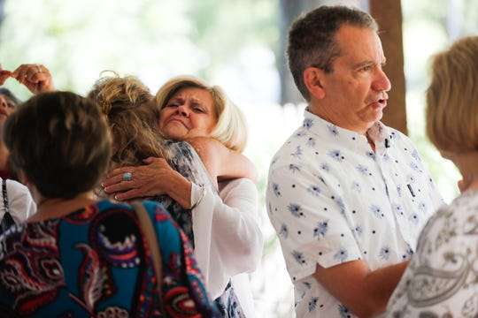 "Debbie Phillips, center, hugs Tina French, center left, of ""The Fabulous Five""  genealogical researchers, as family members like to call the women who helped the siblings find each other, during the siblings first group gathering at Phillip's home in Muncie Ind., on Saturday, Aug. 24, 2019. ""Diamond"" Mike Watson, right, who's in the diamond business, was adopted as an infant. He was able to find his family in 1994, but one sister was not accounted for. After twenty five years, he was able to reunite with her thanks to five female genealogical researchers, DNA, and a facebook page, ""Find Deborah Kay."""