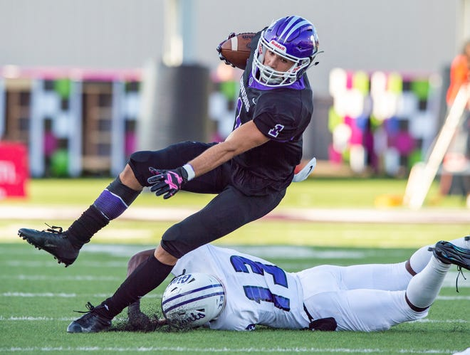 Brownsburg High School's Preston Terrell (1) is tripped up by Ben Davis High School's Capone Powell (13) as he returns a kickoff during the first half of action. Brownsburg High School hosted Ben Davis High School in varsity football action Friday, Aug. 23, 2019.