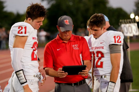 West Lafayette head coach Shane Fry talks with West Lafayette wide receiver Harrison Truitt (21) and West Lafayette quarterback Kyle Adams (12) during the second quarter of an IHSAA football game, Friday, Aug. 23, 2019 at Scheumann Stadium in Lafayette. Lafayette Jeff won, 74-66.