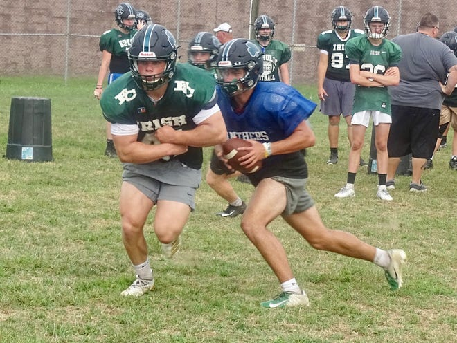 Fisher Catholic quarterback Kaden Starcher fakes a handoff to running back Trey Fabricini during a recent practice. The Irish return a bevy of talent from their 2018 playoff team.