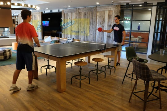 Brothers, John Naaman, right, and James Naaman from Bloomfield Hills play a game of ping-pong at the new Landmark Apartments in East Lansing Saturday, Aug. 24, 2019.