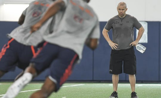 Auburn strength and conditioning coach Ryan Russell watches players go through drills.