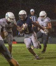 St. James' Austin Gavin runs the ball during the fourth quarter as he tries to avoid a tackle.