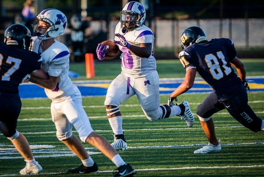 Muncie Central running back Shoka Griffin attempts to run by a defender during a game against Delta during the 2019 season.