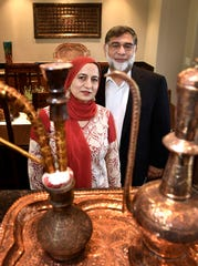 Surrounded by decorative items from Kashmir, Dr. Shazia Fazili and Dr. Farooq Fazili pose for a photo on Aug. 24 in Brentwood. They have not talked to their loved ones in Kashmir for weeks following the lockdown by India.