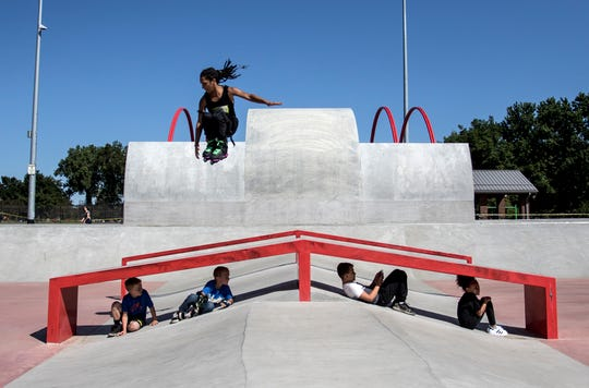 Professional rollerblader, HoodPanda does a trick over a group of local kids at the official opening day of the skate park of Everett Park.