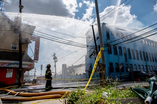 A firefighter looks up at the five alarm fire at 410 Straight Street in Paterson on Saturday August 24, 2019.