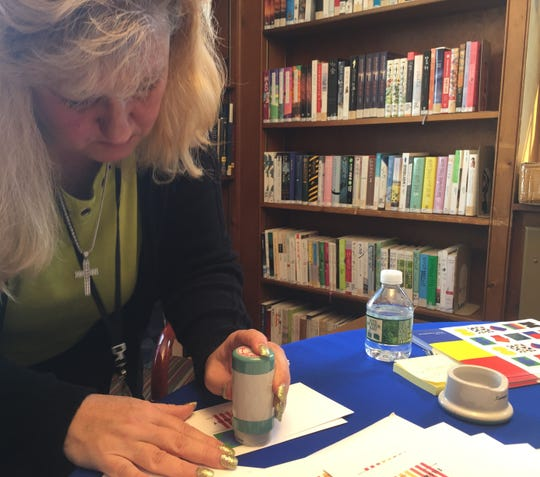 Oradell Postmaster Pauline Ruggieri 'cancels' an envelope, with a commemorative Kelly stamp, at the borough's free public library.