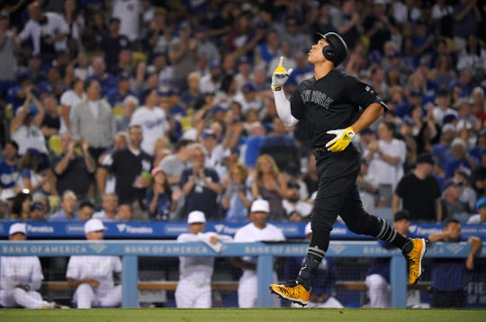 New York Yankees' Aaron Judge gestures before scoring after hitting a solo home run during the third inning of the team's game against the Los Angeles Dodgers Friday, Aug. 23, 2019, in Los Angeles on MLB Players' Weekend.