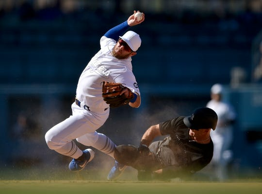 Los Angeles Dodgers second baseman Max Muncy falls while looking to throw to first after New York Yankees' Brett Gardner ran into him, on a grounder hit by Gio Urshela during the ninth inning of a baseball game in Los Angeles, Saturday, Aug. 24, 2019. The Dodgers won 2-1 on MLB Players' Weekend.