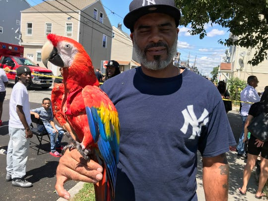 Jorge Dealbe and his parrot DJ just outside the police tape set up on Madison Street. Jorge, his wife Janet and DJ live across the street from Straight and Narrow Paterson. All three have been displaced by the fire.