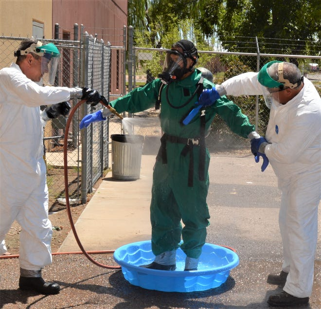 Horacio Palacios, in a Level B response suit, is rinsed off by Juan Chavez and Charles O'Donnell during a training exercise for exposure to hazardous material.