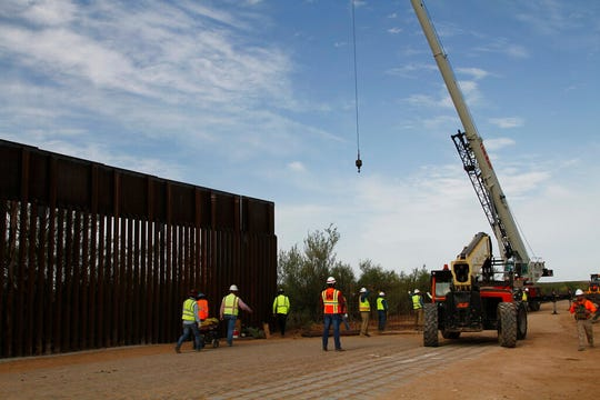 Workers break ground on new border wall construction about 20 miles west of Santa Teresa on Friday, Aug. 23, 2019. The wall visible on the left was built in 2018 with money allocated by Congress, while the new construction is funded by money reallocated from Department of Defense funding.
