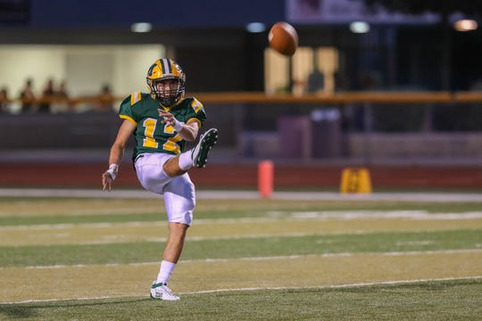 Senior Trojan Marcos Apadaca (12) punts for Mayfield as the Mayfield Trojans and the Atrisco Heritage Academy Jaguars face off for the first game of the season at the Field of Dreams in Las Cruces on Friday, Aug. 23, 2019.