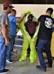Horacio Palacios experiences the Level A full encapsulation response suit during a training exercise.