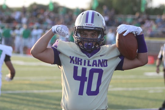 Kirtland Central's Bailey Foutz flexes his muscles after scoring a 7-yard touchdown reception against Farmington during Friday's season opener at Bill Cawood Field in Kirtland.