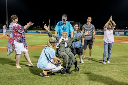 "World War II veteran Albert Lane, 96, spreads his arms wide like the wings of an airplane as players and fans give him a standing ovation during the Blue Wahoos game against the Jackson Generals on Friday. Covenant Care arranged for Lane to fly in a Stearman biplane before the game and to attend the game as part of the organization's ""My Wish"" program."