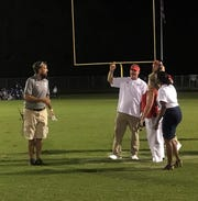Washington Athletic Director Joe Williams (left) and Pine Forest head coach Jason McDonald (red visor) discuss the outcome of Friday's event at Washington.