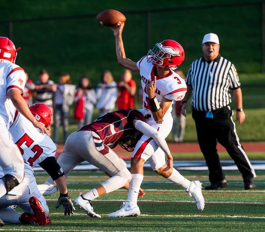 Bermudian Springs quarterback Jay Martinez is hit by New Oxford's Connor Herring as he throws during a game at South Western High School on Friday, August 23, 2019. The Colonials won, 38-7.