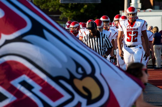 Bermudian Springs' Joe Cooper (52) leads the Eagles onto the field before a game against New Oxford at South Western High School on Friday, August 23, 2019. The Colonials won, 38-7.