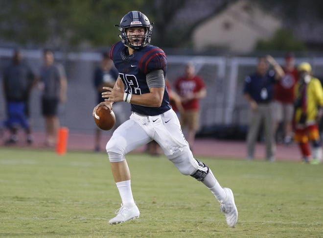 Perry quarterback Chubba Purdy (12) looks for a receiver against Pinnacle's  defense during the first half of their game in Gilbert, Friday, Aug. 23, 2019.