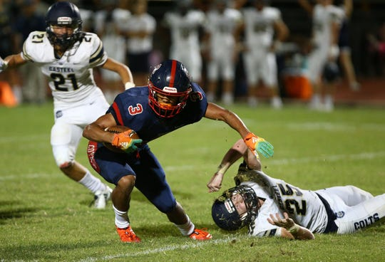 Centennial High running back Jaydin Young (3) shakes-off the tackle by Casteel High defensive end Kyle Pointer (25) in the second half on Aug. 23, 2019 in Peoria, Ariz.