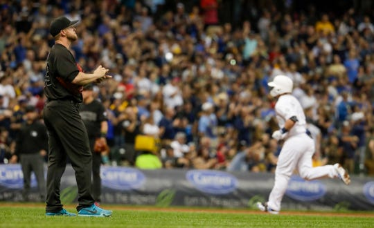 Arizona Diamondbacks starting pitcher Merrill Kelly reacts after giving up a home run to Milwaukee Brewers' Keston Hiura during the fifth inning of a baseball game Friday, Aug. 23, 2019, in Milwaukee.