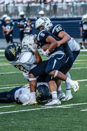 Chambersburg's Jayden Jones is taken down near midfield by Greencastle-Antrim's Ethan Miller on Friday, August 23, 2019. The Trojans won, 56-13.