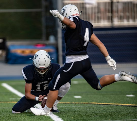Chambersburg's Brady Stumbaugh sets up the ball for kicker Tyler Luther to make a field goal attempt against Greencastle-Antrim on Friday, August 23, 2019. The Trojans won, 56-13.