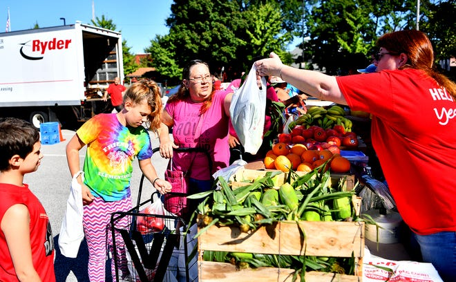 From left, Malaky Baker, 9, Angelee Baker, 11, and Carol Keller, all of York City, are handed a bag of fresh corn on the cob by Dawn Chambers, the Assistant Store Manager, Fresh, of GIANT Food Stores on Pauline Drive as GIANT Food Stores offers a pop-up GIANT produce department offers free produce in the York Revolution Queen Street parking lot in York City, Saturday, Aug. 24, 2019. The pop-up event was organized to help residents affected by the fire a Yorktown Mall on Friday.  Dawn J. Sagert photo