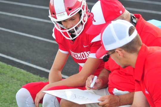 Richmond freshman quarterback Drew VanVleet talks over schemes with the coaching staff. VanVleet threw for 154 yards and four touchdowns in a 41-21 win over Connersville on Friday, Aug. 23, 2019.